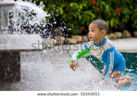 cute preschooler with fancy swimsuit playing with water - stock photo