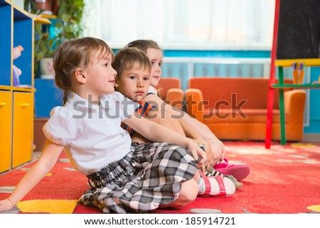 Cute preschoolers sitting on floor and listening to tutor