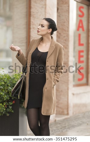 cute pretty brunette woman near a window-shop looking for winter sale . she is wearing a coat and a bag - stock photo