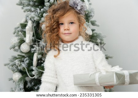 Cute pretty child girl with gift near Christmas tree