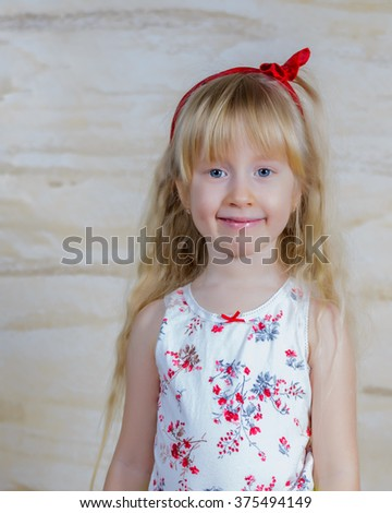 Cute pretty little blond girl with a red bow in her long hair and a happy cheeky grin posing in front of a texture indoor wall at home with copy space