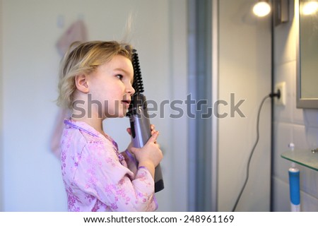 Cute pretty little child, blonde curly toddler girl, playing acting like young adult woman styling hair with round brush dryer looking at her reflection in the mirror in the bathroom - stock photo