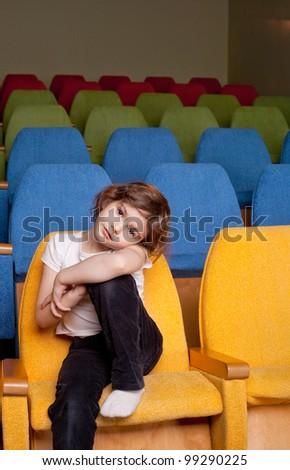 cute pretty little girl sitting in the cinema hall - stock photo