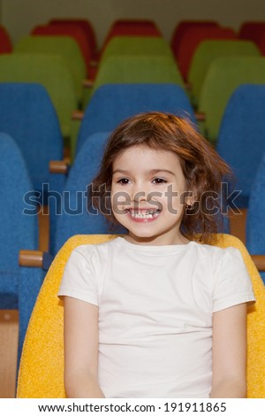cute pretty smiling little girl sitting in the cinema hall - stock photo