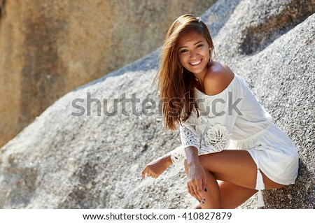 Cute pretty tanned slim girl in white dress on the beach - stock photo