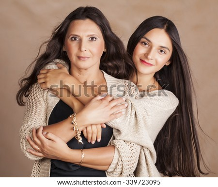 cute pretty teen daughter with mature mother hugging, fashion style brunette makeup close up tann mulattos - stock photo