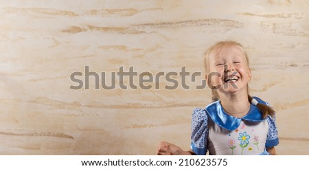 Cute pretty vivacious little girl with her blond hair n braids enjoying a spontaneous candid laugh looking at the camera with a beaming smile, with copyspace - stock photo