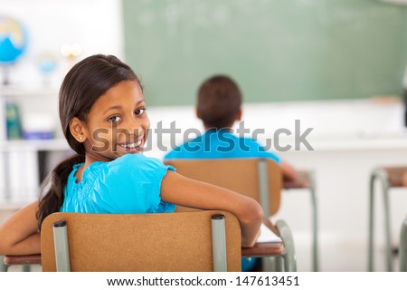 cute primary school girl in classroom looking back - stock photo
