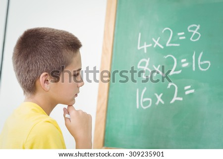 Cute pupil calculating on chalkboard in a classroom in school