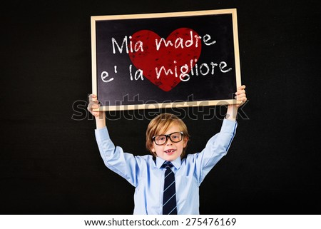 Cute pupil holding chalkboard against black - stock photo