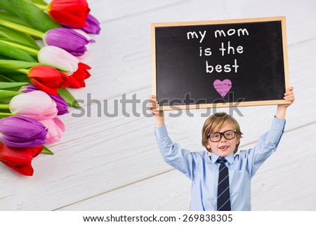 Cute pupil holding chalkboard against tulips on table - stock photo