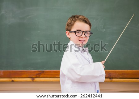 Cute pupil holding stick and pointing blackboard at elementary school - stock photo
