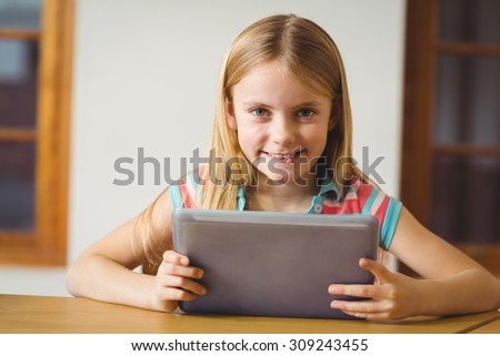 Cute pupil in class using tablet pc at the elementary school - stock photo