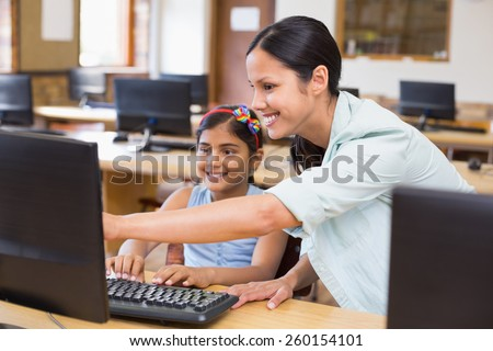 Cute pupil in computer class with teacher at the elementary school - stock photo