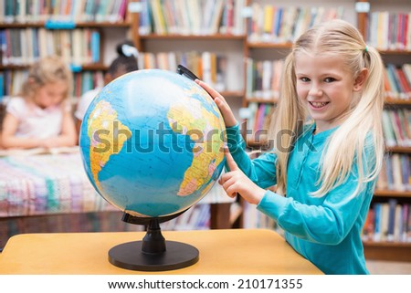 Cute pupil looking at globe in library at the elementary school