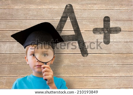 Cute pupil looking through magnifying glass against wooden surface with planks - stock photo