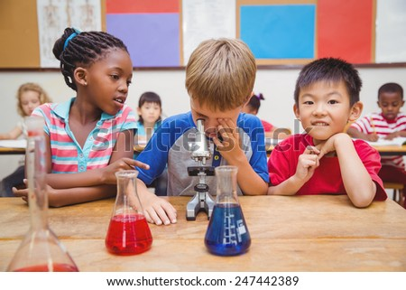Cute pupil looking through microscope at the elementary school - stock photo
