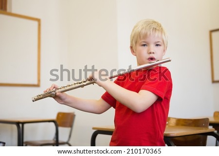 Cute pupil playing flute in classroom at the elementary school - stock photo