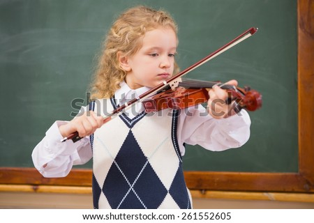 Cute pupil playing the violin at elementary school - stock photo
