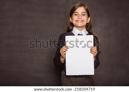Cute pupil showing white page on black background - stock photo