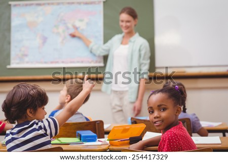 Cute pupil smiling at camera at his desk in classroom at the elementary school