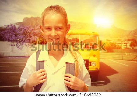 Cute pupil smiling at camera by the school bus against yellow school bus waiting for pupils - stock photo
