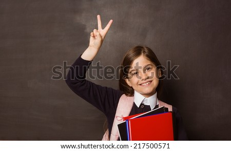 Cute pupil smiling at camera holding books on black background - stock photo