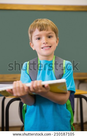 Cute pupil smiling at camera in classroom holding notepad at the elementary school
