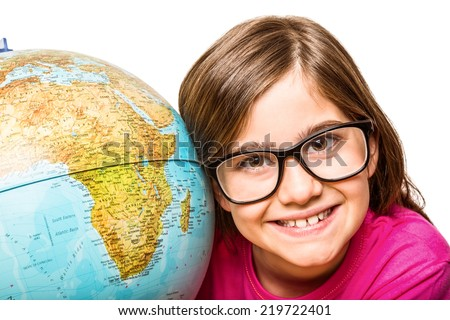 Cute pupil smiling at camera with globe on white background - stock photo