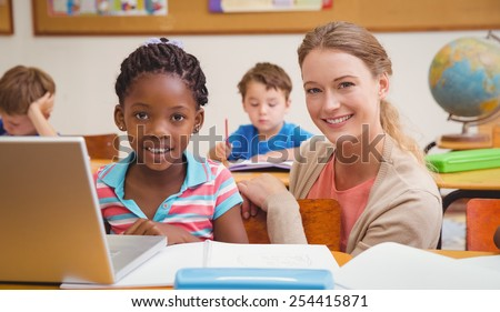 Cute pupil using computer with teacher at the elementary school