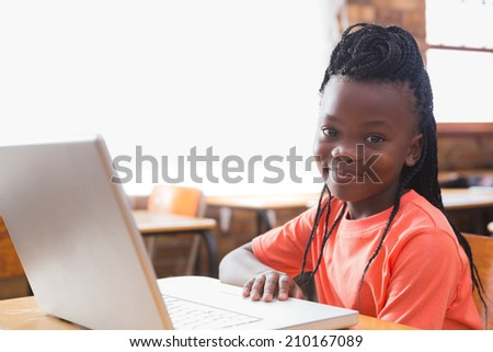 Cute pupil using laptop in classroom at the elementary school