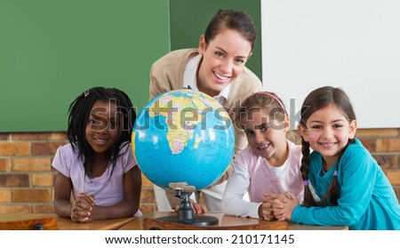 Cute pupils and teacher in classroom with globe at the elementary school - stock photo