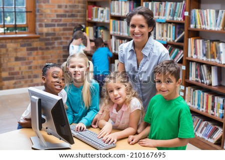Cute pupils and teacher looking at computer in library at the elementary school - stock photo