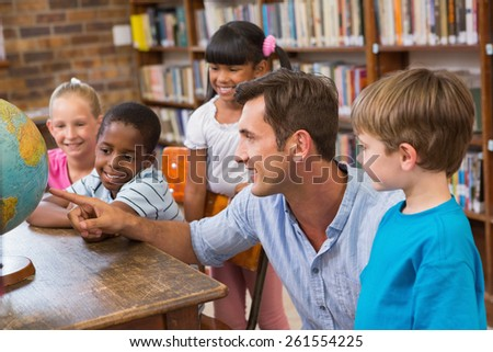 Cute pupils and teacher looking at globe in library at elementary school - stock photo