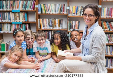 Cute pupils and teacher reading in library at the elementary school - stock photo