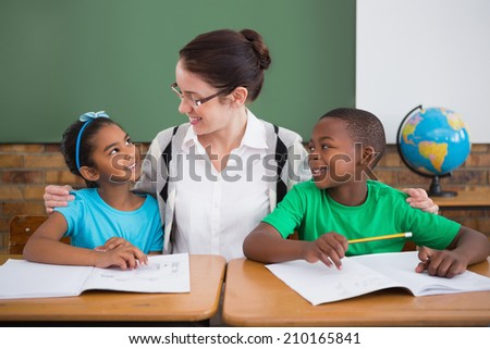 Cute pupils and teacher smiling at each other in classroom at the elementary school