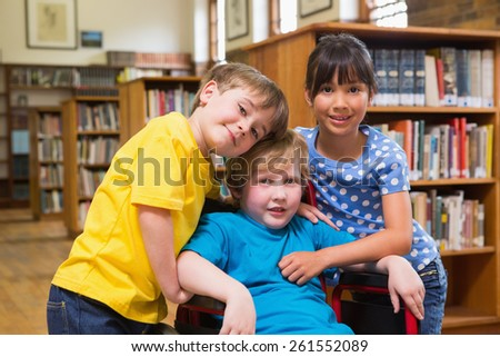 Cute pupils hugging at the library at elementary school - stock photo