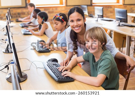 Cute pupils in computer class with teacher at the elementary school - stock photo