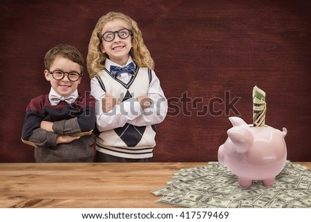 Cute pupils looking at camera against image of a desk - stock photo