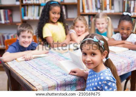 Cute pupils looking at camera in library at the elementary school - stock photo
