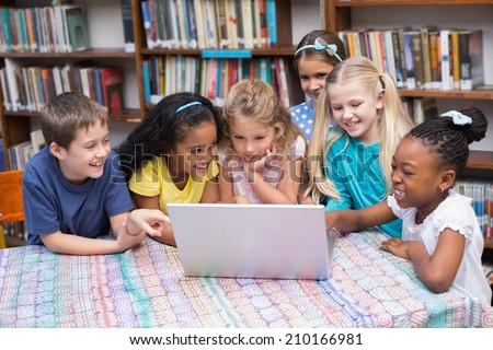 Cute pupils looking at laptop in library at the elementary school - stock photo
