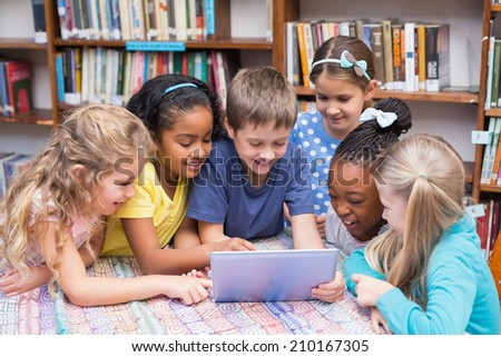 Cute pupils looking at tablet in library at the elementary school - stock photo