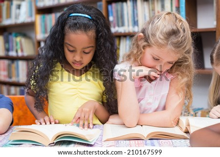 Cute pupils reading books in library at the elementary school
