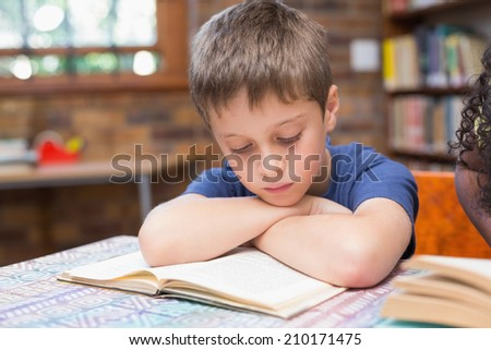 Cute pupils reading books in library at the elementary school - stock photo