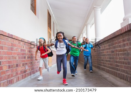 Cute pupils running and smiling at camera in hallway at the elementary school - stock photo