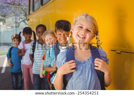 Cute pupils smiling at camera by the school bus outside the elementary school - stock photo