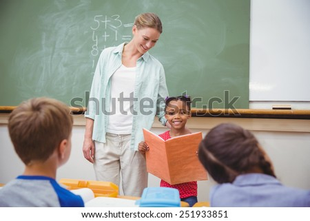 Cute pupils smiling at camera in classroom at the elementary school