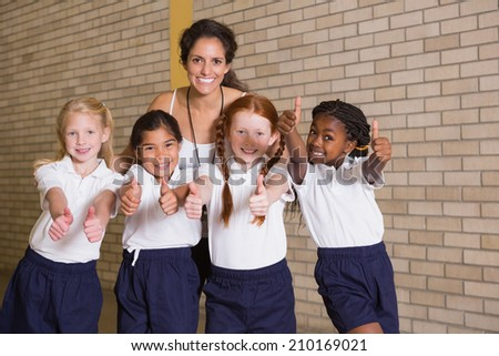 Cute pupils smiling at camera in PE uniform at the elementary school - stock photo