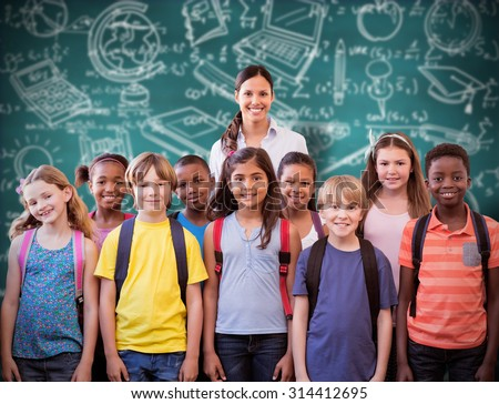 Cute pupils smiling at camera in the hall against green chalkboard - stock photo