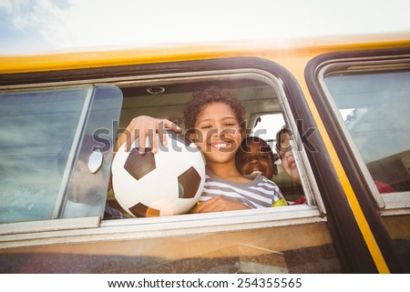 Cute pupils smiling at camera in the school bus outside the elementary school - stock photo